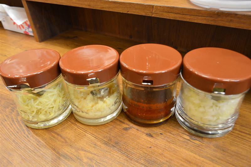 ▲テーブルには醤油や辣油などのほか、「ニンニク」「生姜」「豆板醤」「玉ねぎ」などもある。