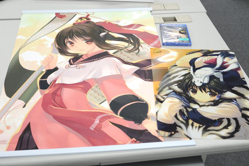 ▲実際に購入! 左がとらのあなの購入特典「甘露樹描き下ろし AJWスエードB2クロスポスター」。右がてアクアプラス関連アイテムを合計7,000円(税込)以上購入で貰える「特製A3クリアポスター」。