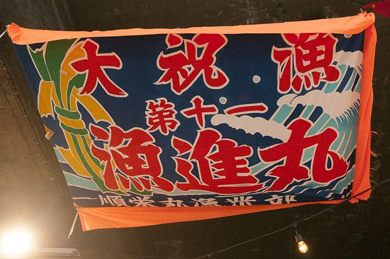▲店長・髙瀨さんが、気仙沼の漁師さんから貸して頂いてる旗を飾らせてもらっているという。